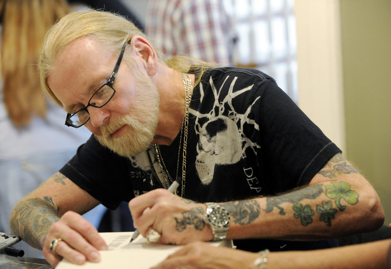 """Gregg Allman signs copies of his book """"My Cross to Bear"""" in Macon, Ga., on Sunday."""