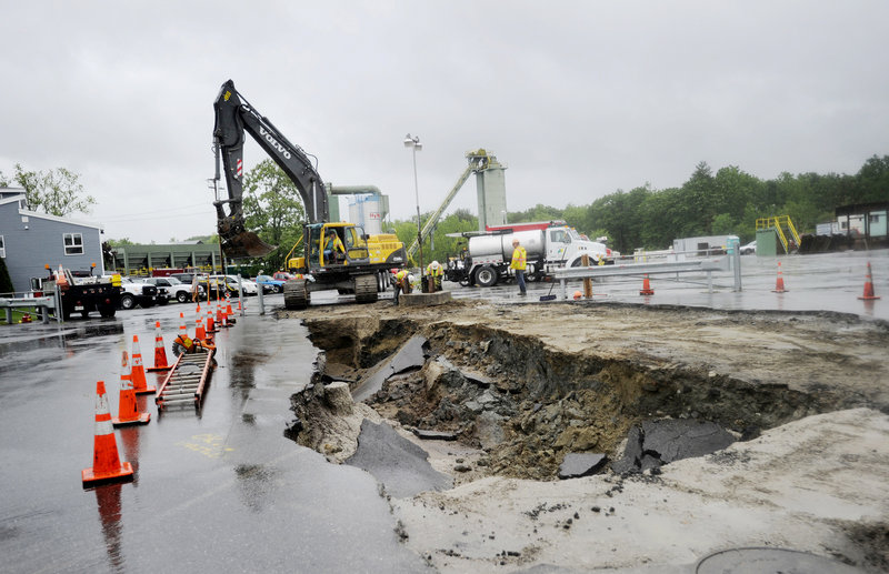 A crew works around a large hole on the property of White Bros. Division of the Lane Construction Corp. in Westbrook. Officials said the stormwater discharge pipe may have ruptured.