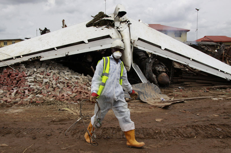 A rescue worker walks past the wreckage of a plane in Lagos, Nigeria, on Monday. The passenger plane carrying 153 people crashed in Nigeria's largest city.