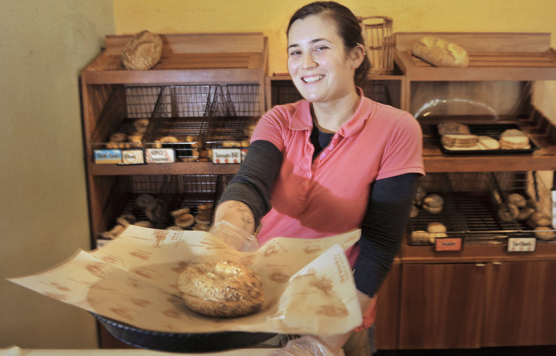 Store manager Amy Christiansen offers a customer a toasted bagel sandwich at The Works Bakery Cafe on Temple Street in Portland.
