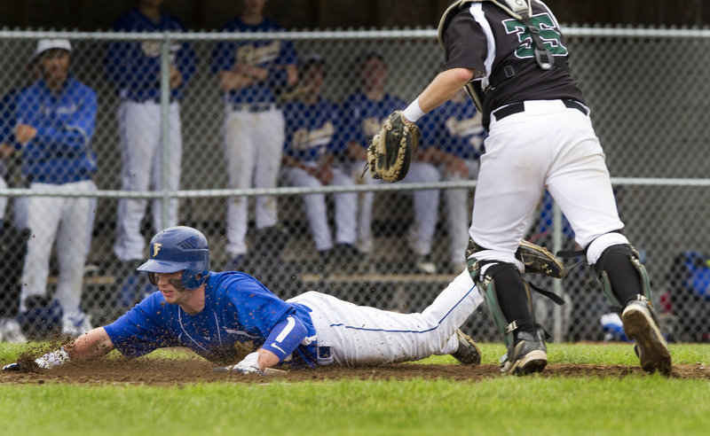 Grayson Beressi of Falmouth dives into the plate to score Thursday during a five-run third inning that helped the Yachtsmen earn a 7-3 victory against Spruce Mountain in their Western Class B quarterfinal. The Spruce Mountain catcher is Brandon Hodges.