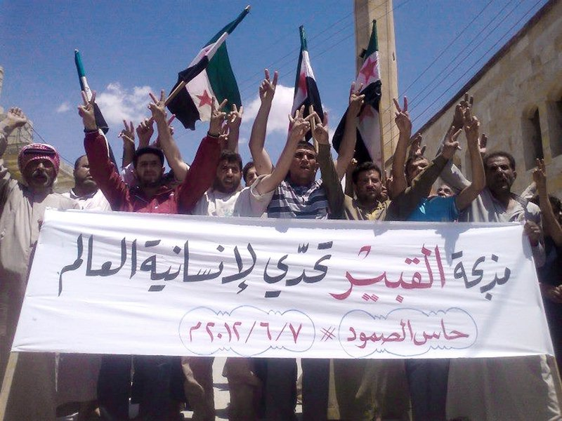 "In an image provided by Edlib News Network, opponents of the Syrian regime chant slogans Thursday and hold a banner in Arabic that reads, ""Al-Qubair massacre challenges the world's humanity"" in the northern village of Hass. There were reports of up to 80 people killed in al-Qubair, but Syrian officials called the reports ""absolutely baseless."""