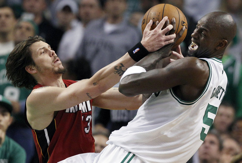 Kevin Garnett of the Boston Celtics, right, tries to keep a rebound from Mike Miller of the Miami Heat during Miami's 98-79 victory Thursday night.