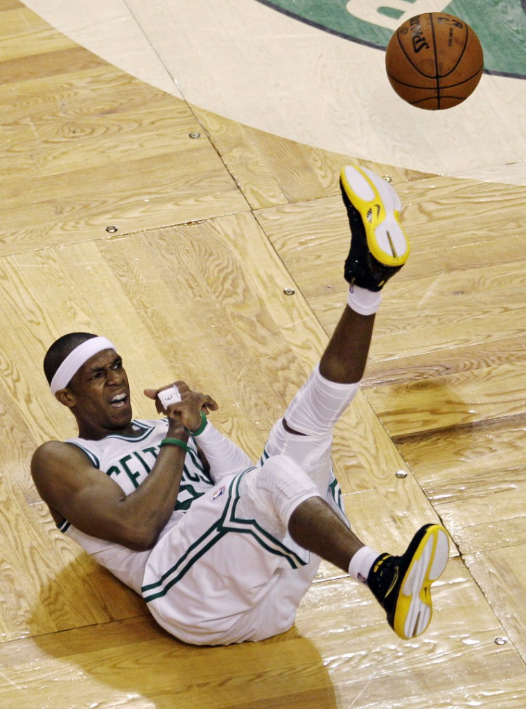 The ball goes one way, Rajon Rondo of the Celtics goes the other after a collision with Mario Chalmers of the Miami Heat.