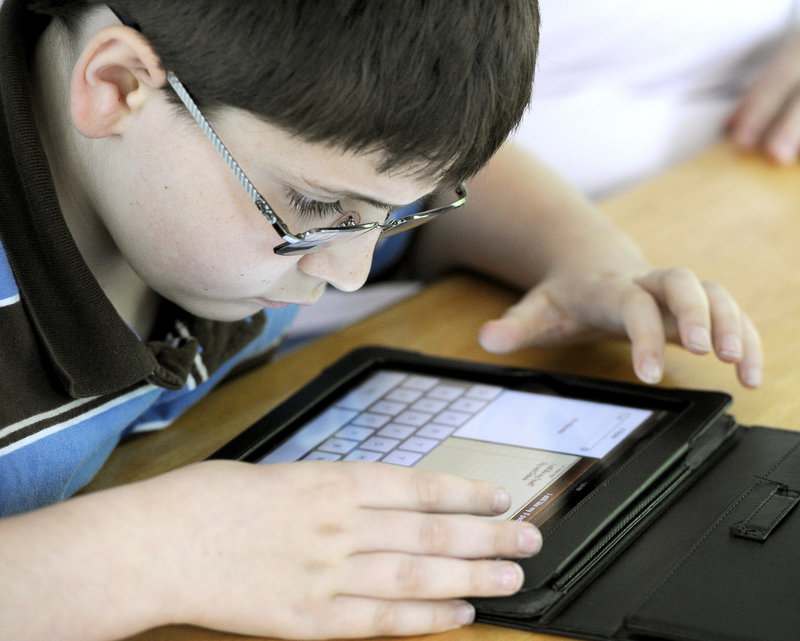 Zackery Dubois, 10, studies spelling on the iPad he received from the Robbie Foundation to help with his schooling.