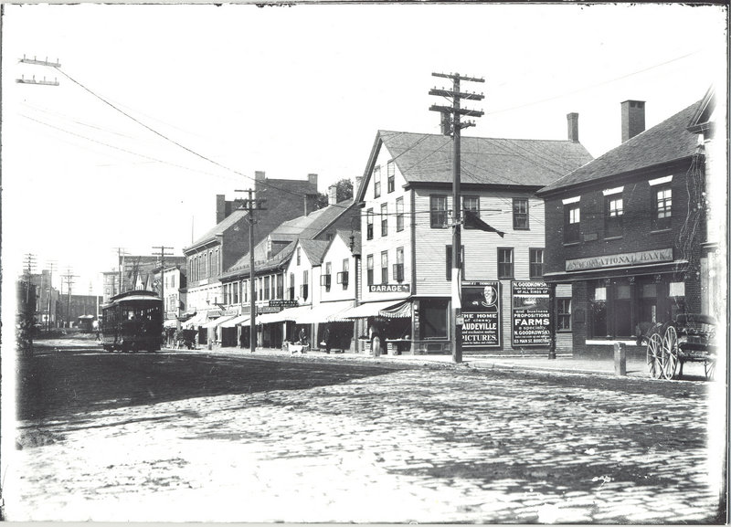 An electric trolley, above, rolls its way down Main Street in Saco circa 1920. Saco National Bank can be seen on the right at Main and Storer streets. Farther up the street is a garage covered with advertisements, as well as Edwin W. Fay's grocery store. Below, as seen in a photograph taken Thursday, the same stretch of road as it appears today.
