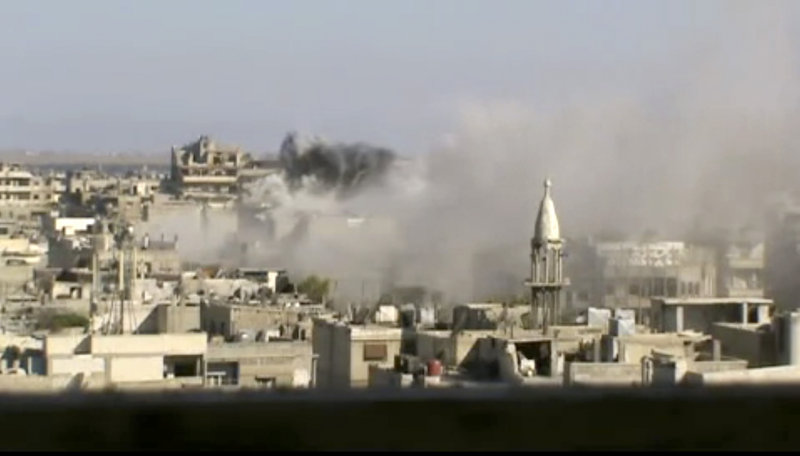 Image made from amateur video released by Shaam News Network and accessed Friday purports to show explosions in the Khaldiyeh area of the central city of Homs, Syria.