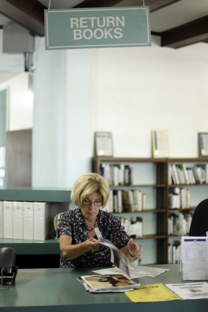 Library clerk Jane Stahl organizes items at a branch of the San Diego, Calif., Public Library. The city's pension-fund payments soared to $231 million this year, leaving less money for services like the libraries.