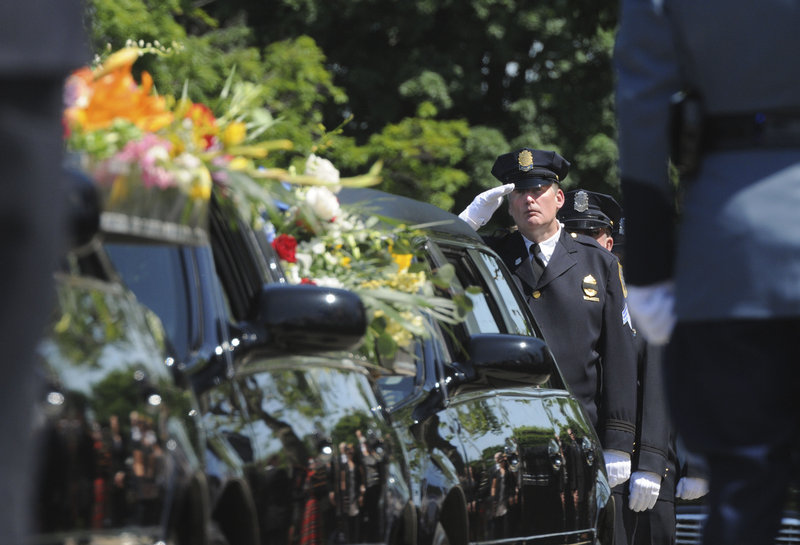 Springfield, Mass., police Sgt. Neil Maloney salutes the hearse bearing the casket of fallen Springfield police Officer Kevin Ambrose on Friday in Springfield.