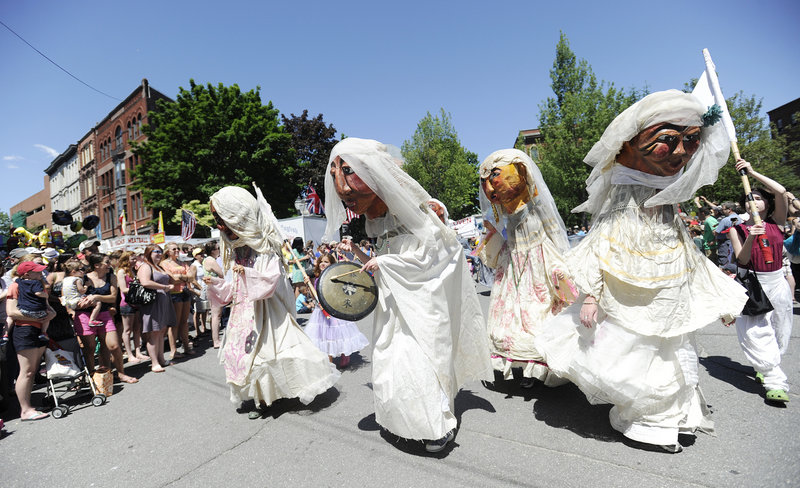 Performers with Shoestring Theater make their way down Exchange Street during the parade at the Old Port Festival in Portland on Sunday. Thousands of people filled the city to listen to music, watch street performers and check out the vendors.
