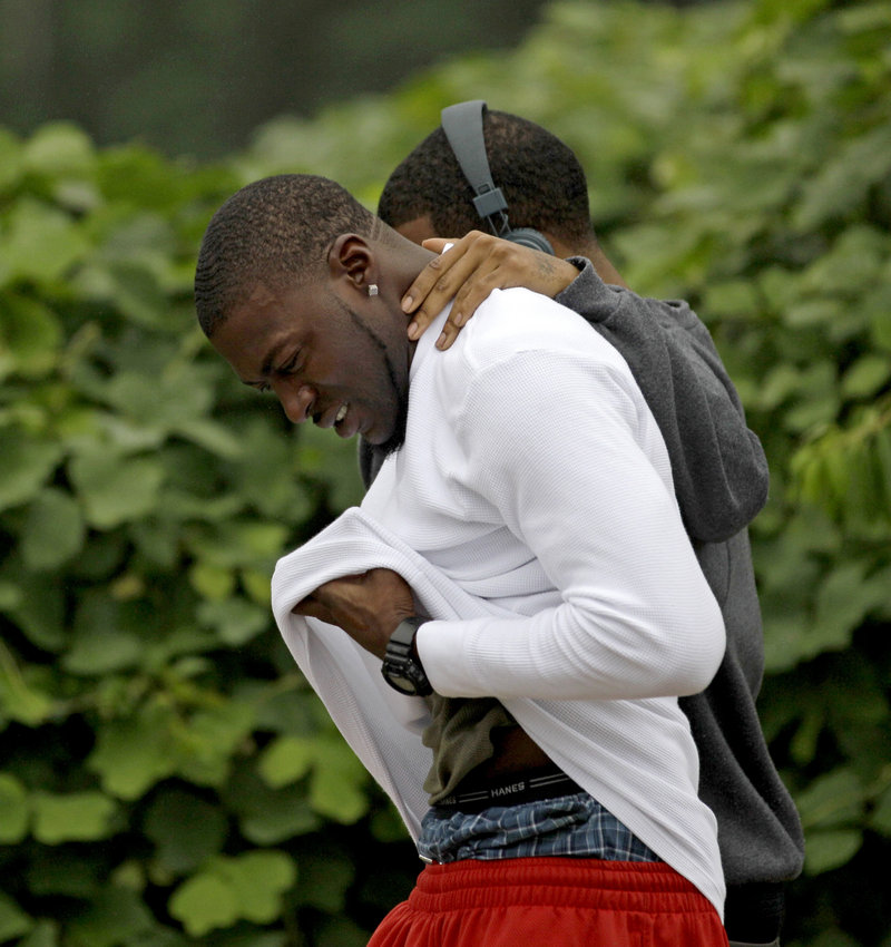 Mourners leave a housing complex at the scene of an overnight shooting Sunday in Auburn, Ala. A gunman killed three people, including two former Auburn University football players.