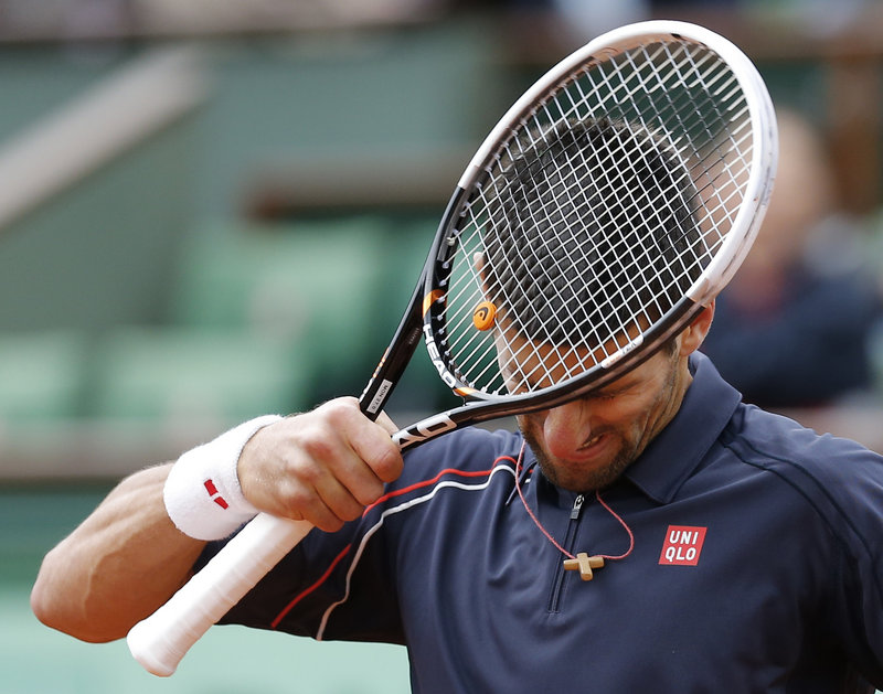 Racket meets head as Novak Djokovic laments a lost point. He was trying to become only the third man to win four major tournaments in a row.