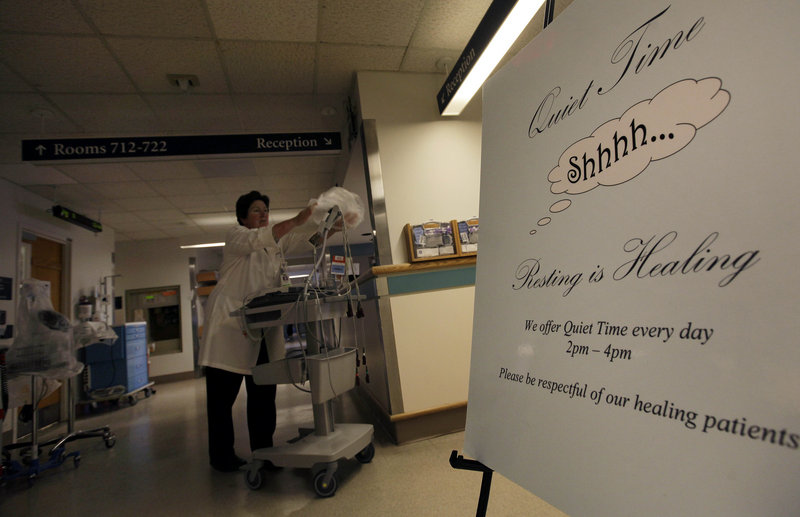 "A sign is posted for ""quiet time"" while Nursing Director Theresa Capodilupo works under dimmed lighting in the hall of the Surgical Trauma Unit at Massachusetts General Hospital in Boston on Friday."