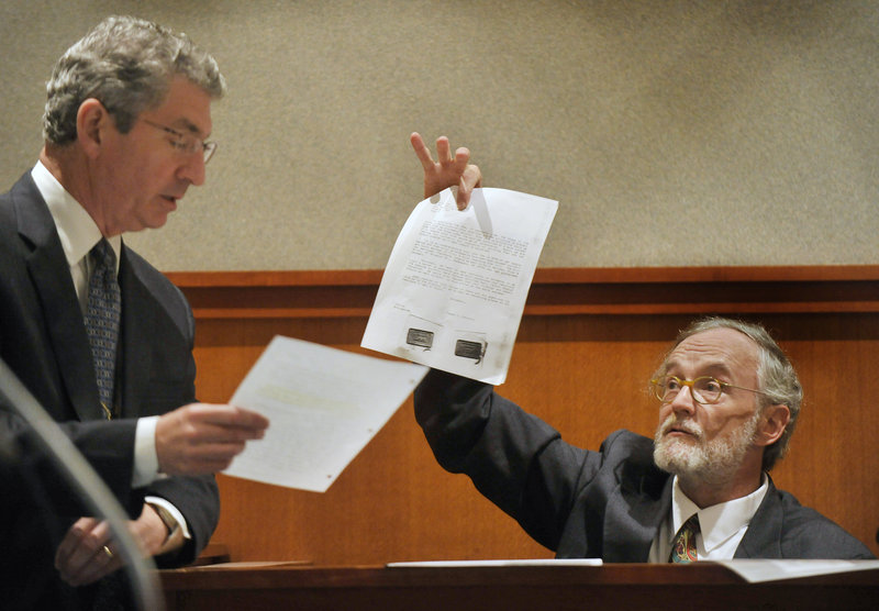 Deputy Attorney General William Stokes, left, verifies pieces of evidence with Thomas Connolly, Dennis Dechaine's former defense attorney, who was called as a witness at the hearing on Dechaine's latest effort to obtain a new trial.