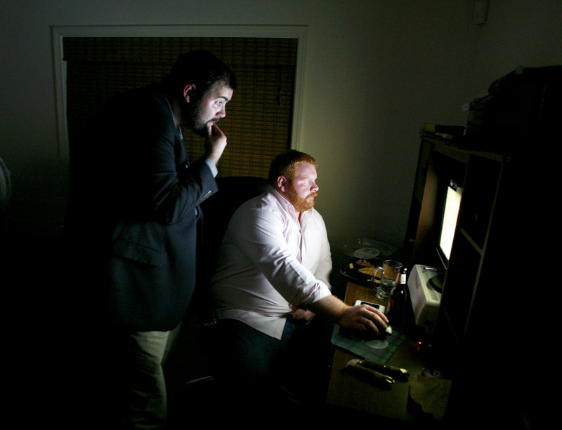 Patrick Calder, left, and his deputy campaign manager, Andrew Love, monitor the neck-and-neck election results Tuesday night on a computer at Calder's home in Portland.