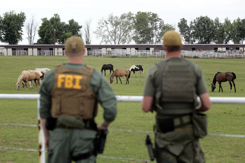FBI agents overlook a horse ranch under investigation Tuesday in Lexington, Okla. Federal agents raided the ranch Tuesday, alleging its owner was using the horse-breeding operation to launder drug money.