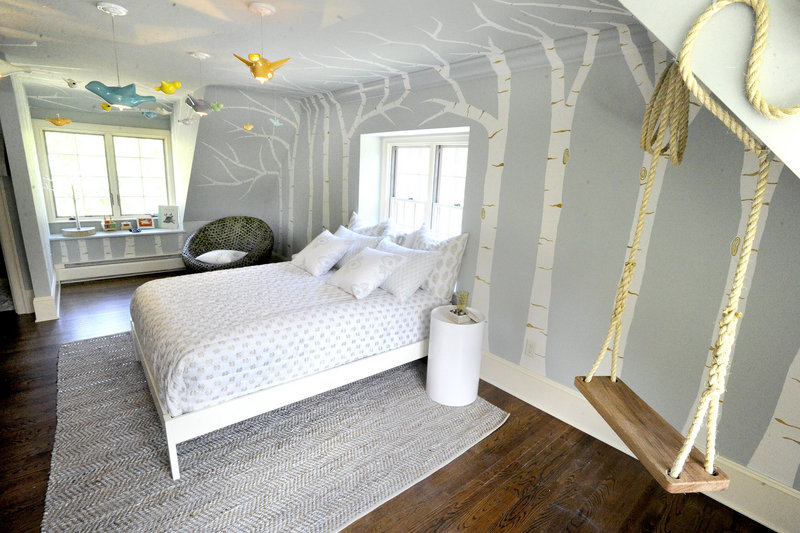 A child's bedroom, decorated by Nicki Bongiorno of Spaces Kennebunkport, features white birch trees painted on the walls and ceiling, hanging light fixtures shaped like birds, and a rope swing.