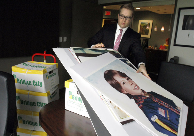 Attorney Peter Janci sets court case displays upon boxes full of records from the Boy Scouts of America in Portland, Ore. The state Supreme Court ordered their release Thursday.