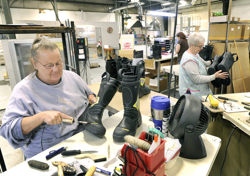 Laurie Auger cleans glue from boots prior to shipping.