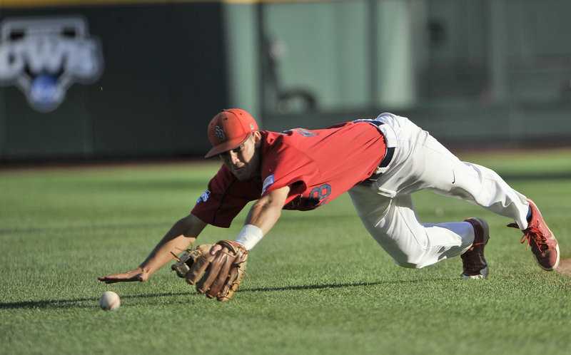 Stony Brook shortstop Cole Peragine can't reach a single by UCLA's Pat Valaika during their College World Series opener Friday in Omaha, Neb. UCLA won, 9-1.