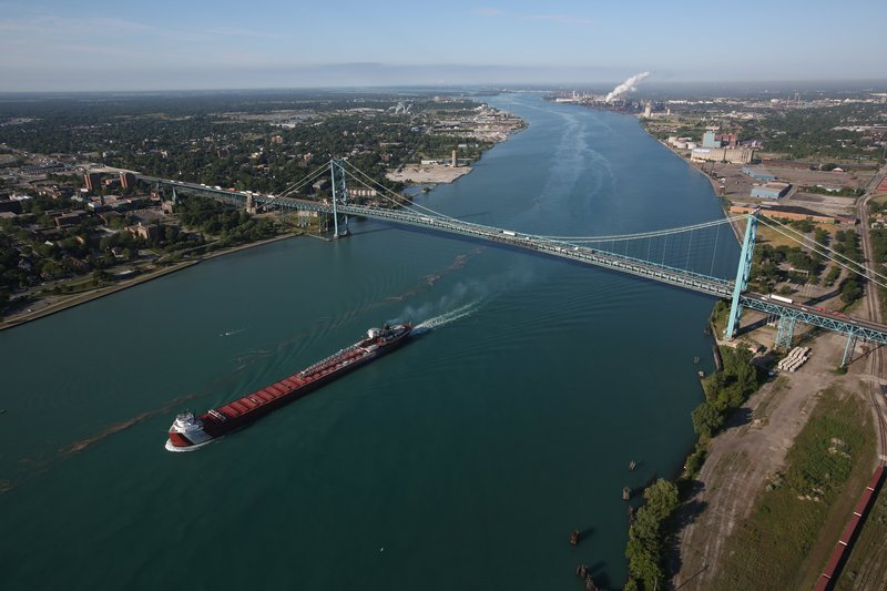 In this aerial photo, a freighter passes by the Ambassador Bridge that links Detroit on the right and Windsor, Ontario, on the left on Thursday.