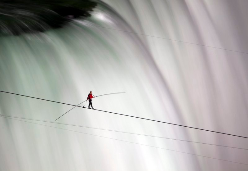 Nik Wallenda walks over Niagara Falls on a tightrope Friday, becoming the first person to do so. ABC television, a sponsor of the event, insisted he wear a safety tether.