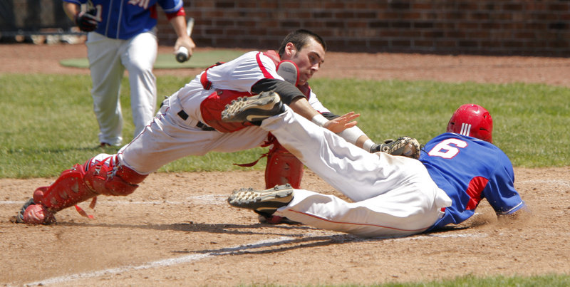 Travis St. Pierre of Messalonskee dives across the plate as Scarborough catcher Conor McCann applies the tag during the Class A baseball final. St. Pierre was called out, but Messalonskee earned its first Class A title with a 6-3 win.
