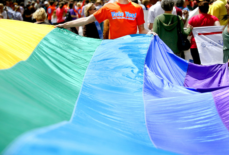 Chris Sawyer of South Portland, with Mainers United for Marriage, helps carry a rainbow flag during the Southern Maine Pride Parade and Festival on Congress Street in Portland on Saturday.