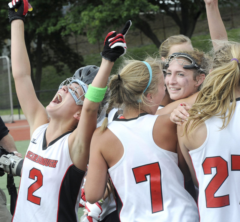 Jess Meader, left, leads the celebration Saturday after Scarborough continued its domination of Class A girls' lacrosse, beating Brunswick 11-9 for its third consecutive state championship.