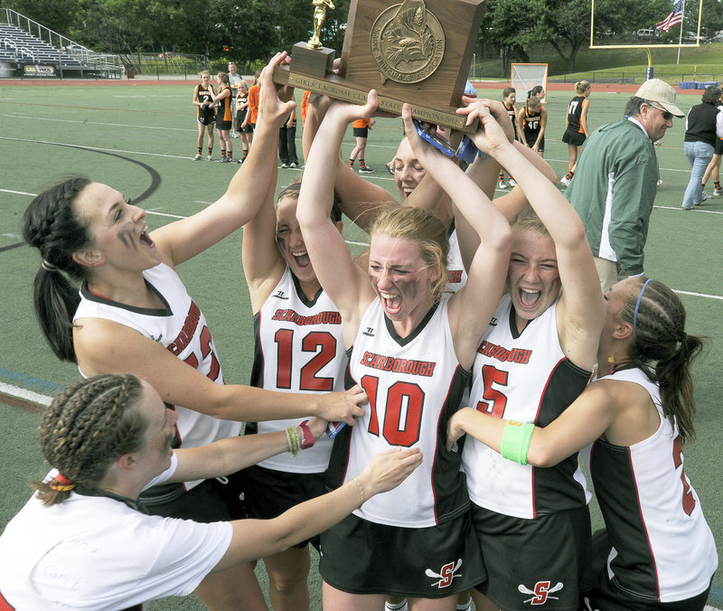 Breanna Good, left, Laura Przybylowicz (12), Maggie Smith (10) and Kelsey Howard (5) help raise the championship plaque after Scarborough held off Brunswick 11-9 to win its third consecutive Class A girls' lacrosse title.