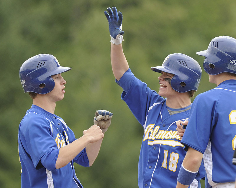 Jeremy Lydick, left, is congratulated by Drew Proctor after scoring on Ryan Conley's two-run double -- the only runs in Falmouth's 2-0 win over Foxcroft Academy for the Class B baseball championship.
