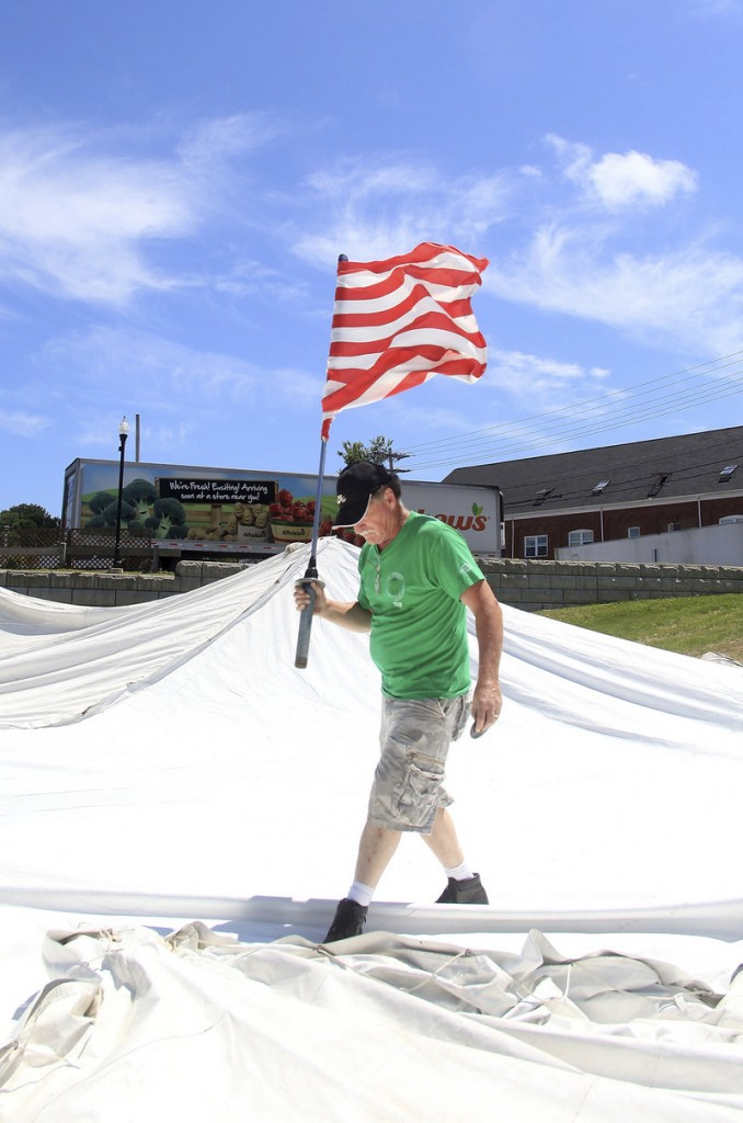 Joseph LeBlond, production manager for La Kermesse, carries an American flag on Sunday that will fly atop the main entertainment tent during the festival, which runs Thursday through Sunday in downtown Biddeford.