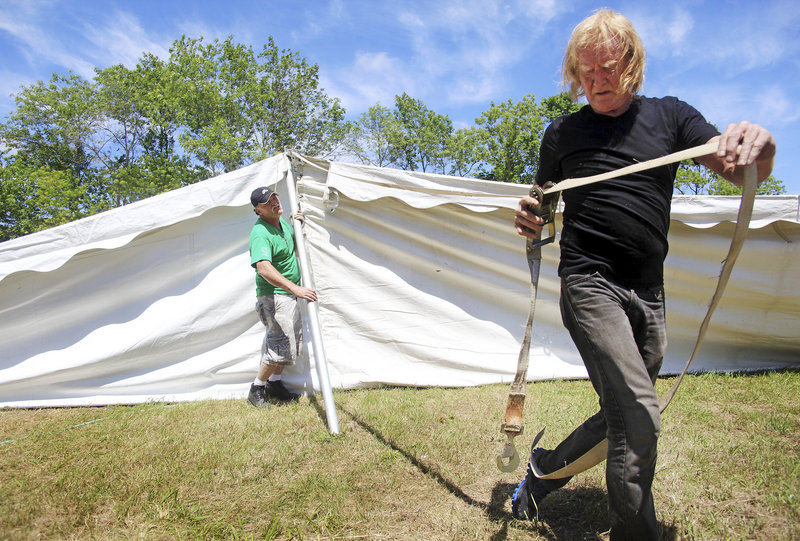 Tom Brady, front, and Joseph LeBlond work together to set up the main entertainment tent on Sunday for the 30th anniversary of La Kermesse festival in Biddeford.