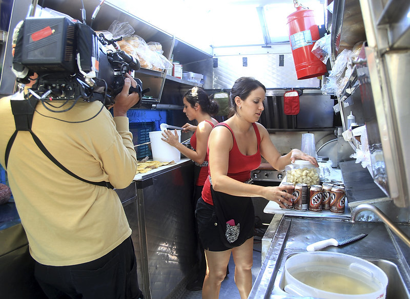 "Lisa Nativo, right, and Jessica Stambach of Nonna's Kitchenette are filmed by Dave Landry as they prepare to open their truck during the Food Network's ""The Great Food Truck Race"" on Commercial Street in Portland on Sunday."