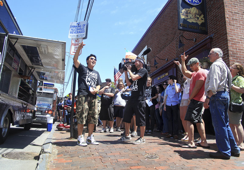 "Ted Kim, center, leads the gathering crowd in a cheer just before opening the Seoul Sausage truck as ""The Great Food Truck Race"" is filmed for the Food Network in Portland outside of Ri Ra's Irish Pub on Commercial Street on Sunday."
