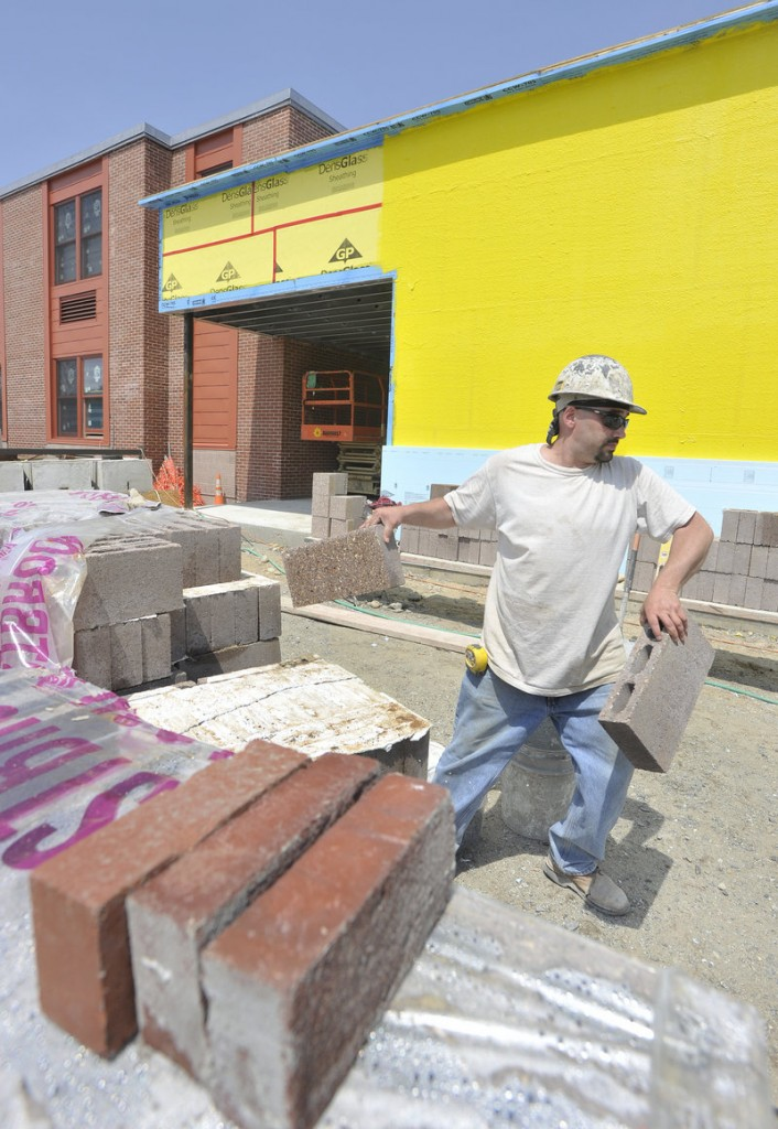 Jared Shaw, a mason tender from South Paris, moves bricks at a newly built section of Lake Region High School. The $13.8 million project, begun in the fall of 2010, addresses concerns in accreditation reports over the 42-year-old building's air quality and space constraints.