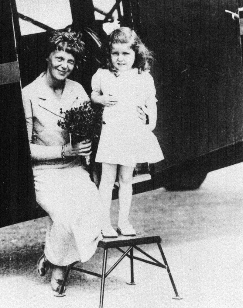 Amelia Earhart gets flowers from Gladys Chase, age 5, of Augusta on Aug. 14, 1934, at the Augusta airport.