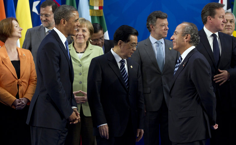 President Obama looks to Mexican President Felipe Calderon as he joins other leaders at the G20 Summit on Monday in Los Cabos, Mexico. They are, from left, Australian Prime Minister Julia Gillard, Spanish Prime Minister Mariano Rajoy, German Chancellor Angela Merkel, Chinese President Hu Jintao, Colombian President Juan Manuel Santos, Calderon and British Prime Minister David Cameron.