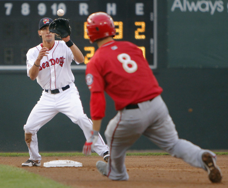 Derrik Gibson of the Portland Sea Dogs takes a toss ahead of Sean Nicol of Harrisburg before throwing to first for a double play Tuesday night during a 14-0 victory at Hadlock Field.