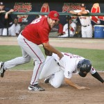 Peter Hissey of the Sea Dogs tumbles next to Harrisburg pitcher Robert Gilliam after scoring on a passed ball Thursday night. Hissey was a home run shy of a cycle, leading the Sea Dogs to a 6-1 victory.