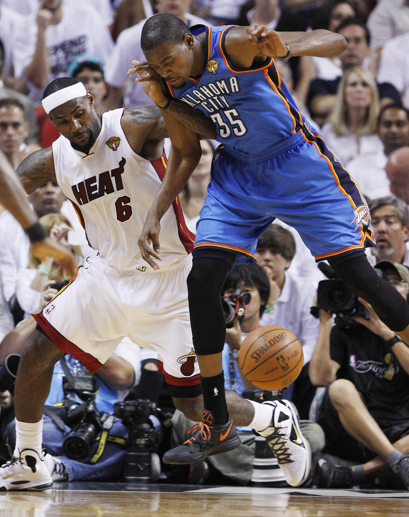 LeBron James, left, of the Miami Heat and Kevin Durant of the Oklahoma City Thunder compete for a loose ball Thursday night. Miami won the NBA title with a 121-106 victory.