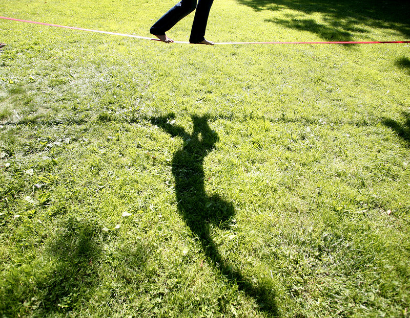 Evan Lewis of Portland practices his slacklining skills Thursday as he balances on a nylon webbing tied to two trees at Deering Oaks park in Portland.