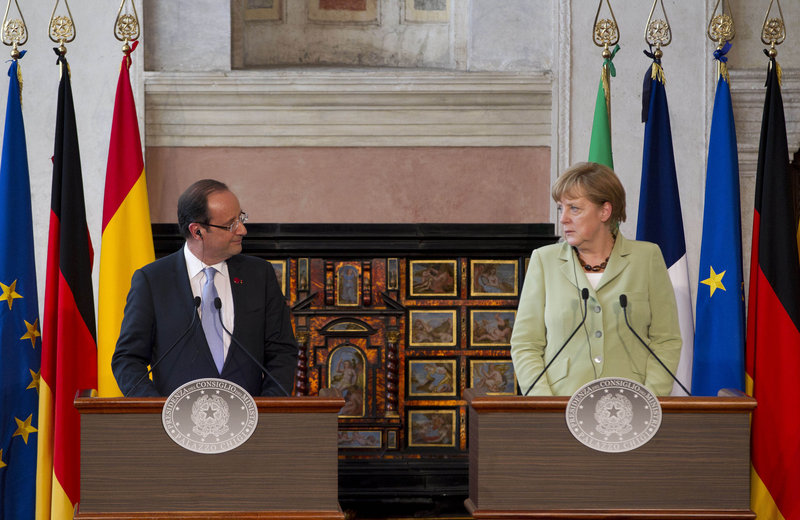 French President Francois Hollande, left, and German Chancellor Angela Merkel end a Friday meeting with Italian Premier Mario Monti and Spanish Premier Mariano Rajoy.