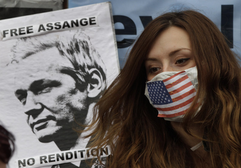A supporter of WikiLeaks founder Julian Assange sits outside the Ecuadorean Embassy in London on Friday. Assange is trying to gain political asylum in Ecuador.