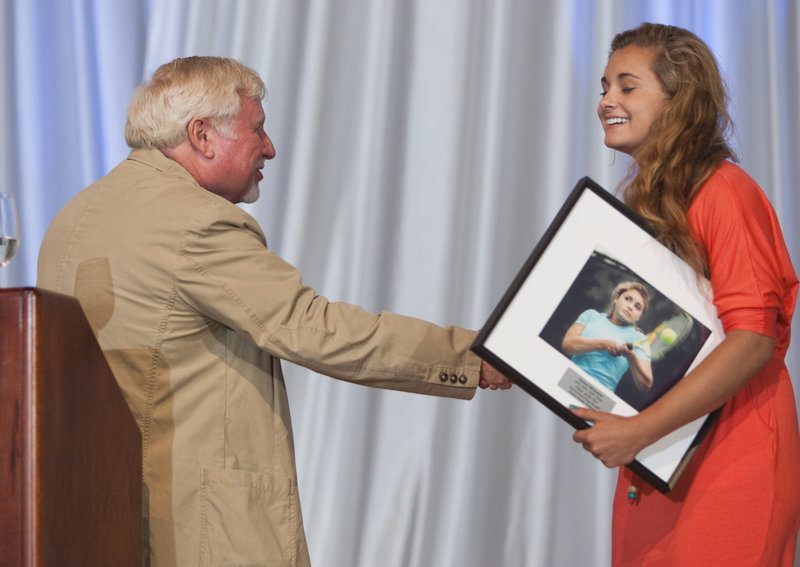 Maisie Silverman, the girls' tennis player of the year, receives her plaque from Steve Solloway, a Press Herald columnist and master of ceremonies. The top athletes in each high school sport were recognized with a short vignette, then awarded a framed photo of themselves in competition.