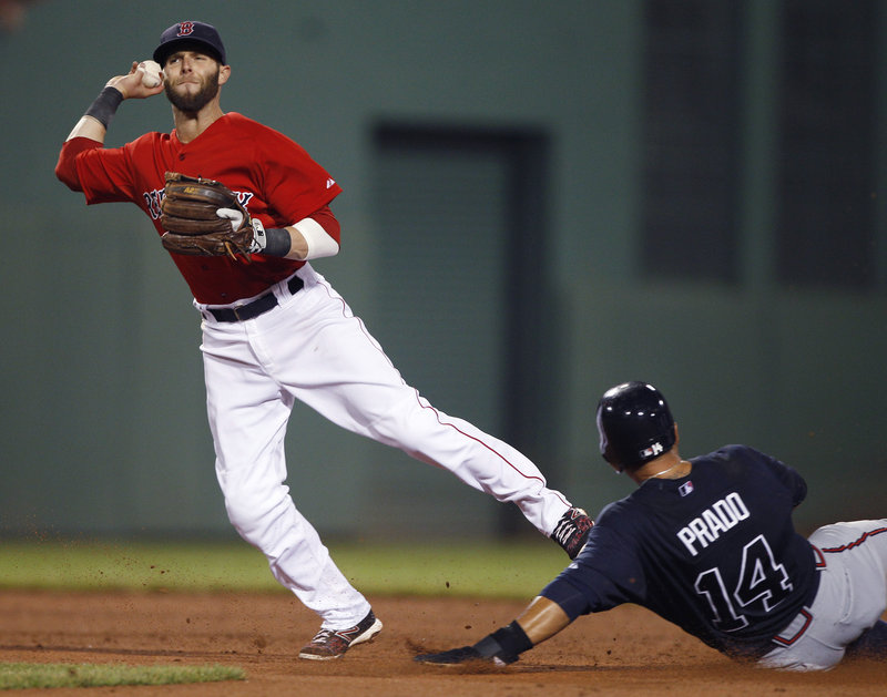 Dustin Pedroia of the Boston Red Sox throws to first in the fifth inning Friday night after forcing Martin Prado of the Atlanta Braves at second. The throw was too late to complete a double play on Dan Uggla. Atlanta won, 4-1.