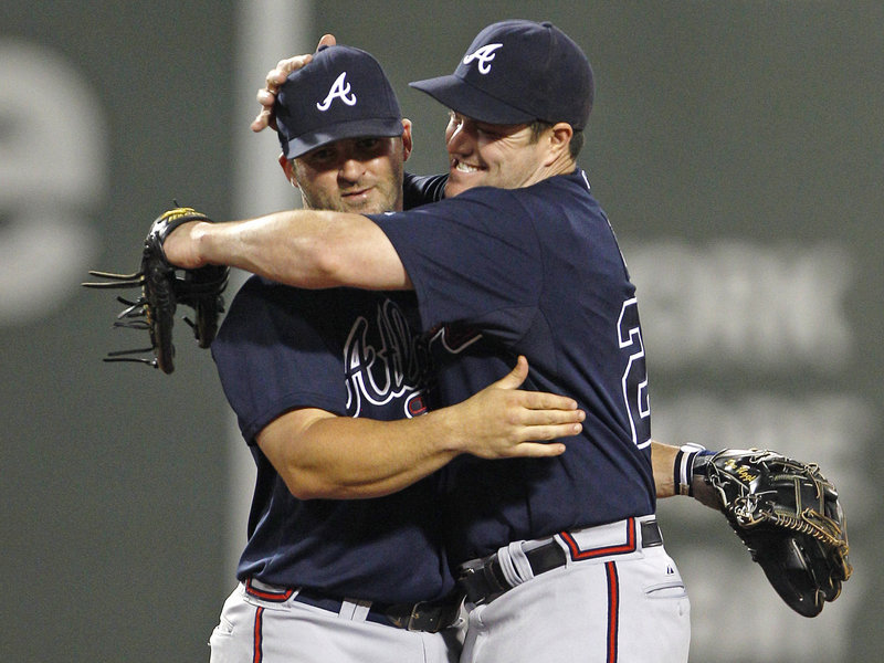 Right fielder Matt Diaz of the Atlanta Braves, right, hugs second baseman Dan Uggla after the final out at Fenway Park. The teams meet again tonight.