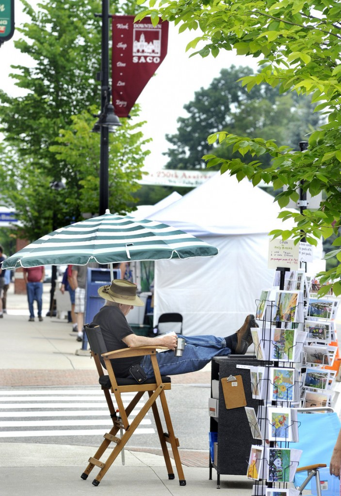Artist Joseph Barnett of Kennebunk relaxes after setting up his display Saturday.
