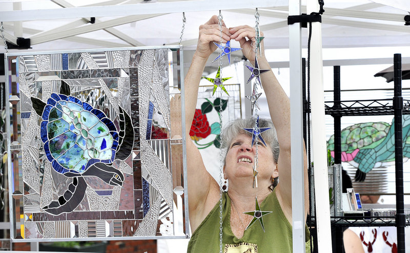 Stained glass artist Peggy Pulling of Gorham sets up her display at the 42nd Saco Arts Festival highlighting Saco's 250th Anniversary Celebration.