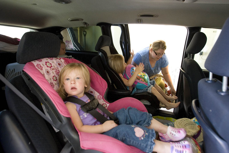 Luci Christiansen, 2, waits for her mother, Lisel, to finish loading their van as they prepare to leave their home in Eagle Mountain, Utah, on Friday.